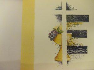 Das Bild zeigt eine Kommunionskarte. Die linke Seite ziert ein gelber Streifen, der Hintergrund ist weiß. Ein Kelch mit Weintrauben, der von einem Kreuz überblendet wird ist darauf abgebildet. Blaue Schattierungen setzen das weiße Kreuz vom Hintergrund ab und bieten Hintergrund für schwer lesbaren handschriftlichen Text.