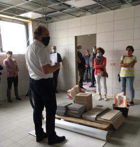 Bürgermeister Paul Kreber steht zu einer Gruppe von Zuschauern gewandt in einem Raum des neuen Bürgerzentrums. Der Raum ist noch im Bau befindlich. Die Decke ist noch nicht fertig und auf dem Boden sind Werkzeuge und Baumaterial zu sehen. Manche personen stehen außerhalb des Raumes, alle tragen einen Mund-Nase-Schutz.