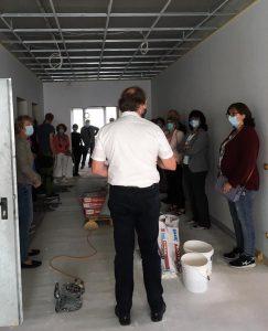 Bürgermeister Paul Kreber steht zu einer Gruppe von Zuschauern gewandt in einem Raum des neuen Bürgerzentrums. Der Raum ist noch im Bau befindlich. Die Decke ist noch nicht fertig und auf dem Boden sind Werkzeuge und Baumaterial zu sehen.